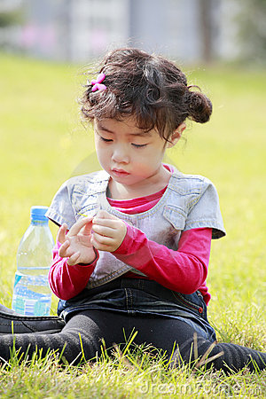 Asian little girl playing on grass