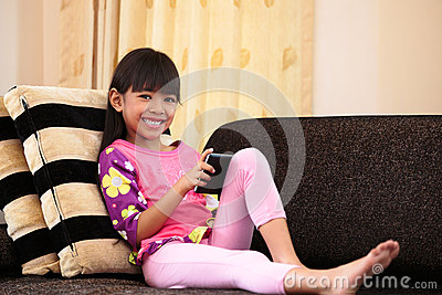 Asian little girl playing with tablet at home
