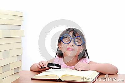 Asian little girl reading a book