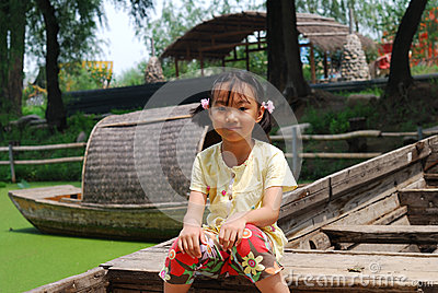 Asian little girl sitting on a wood boat