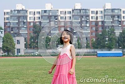 Asian little girl  stood on the grass