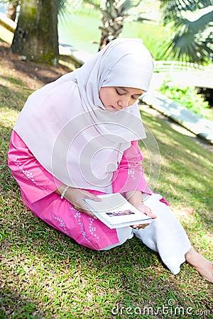 Asian Malay Muslim woman reading