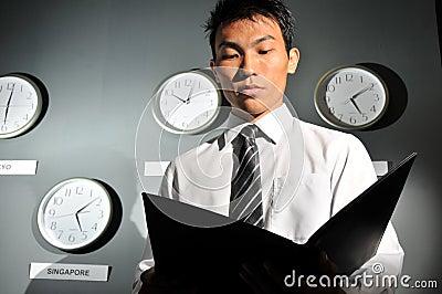 Asian Male Boss scrutinizing office work