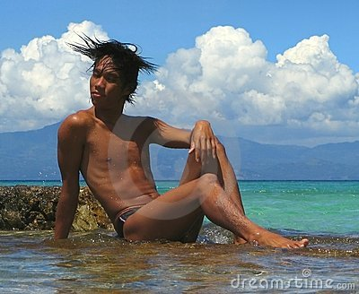 Asian male on rocks, swimwear.
