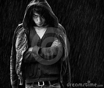Asian man with cross hands under rain