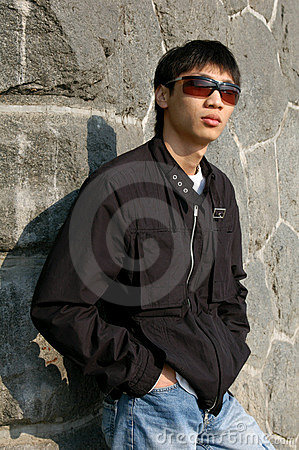 Asian Man Leaning against a Wall