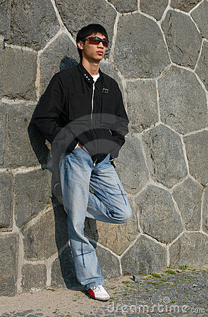 Asian Man Leaning Against A Wall Royalty Free Stock Photo