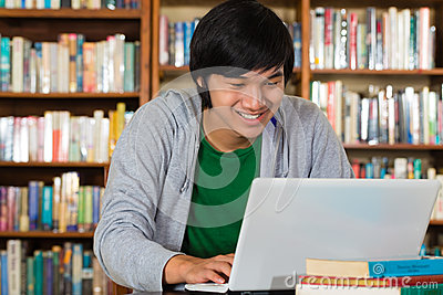 Asian man in library with laptop