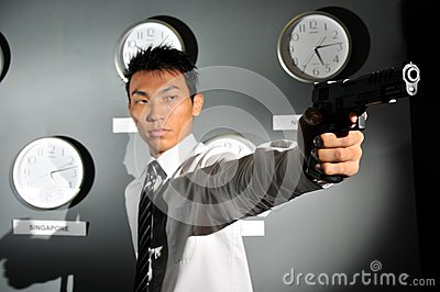Asian Man in office with a Gun