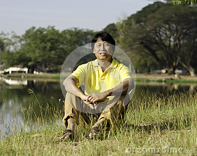 Asian man sitting  in the park
