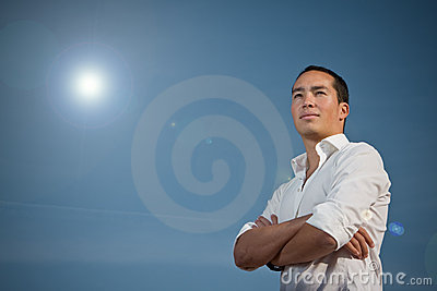 Asian man standing with arms folded