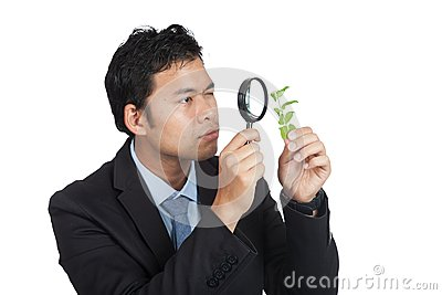 Asian man use  magnifying glass observe leave