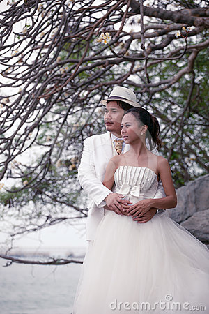 Asian man and woman in wedding suit hug with love