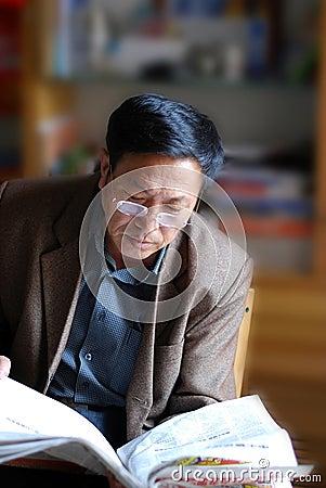 Asian mature man reading news