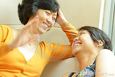 Asian mother happy talking with teen daughter