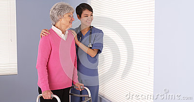 Asian nurse and elderly patient standing by window