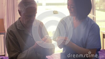 Asian nurse giving medical pills to elderly man seated on the bed, sunlight coming from outdoor stock video footage