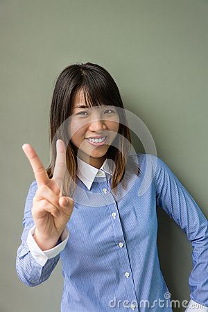 Asian office girl showing victory sign in grey background