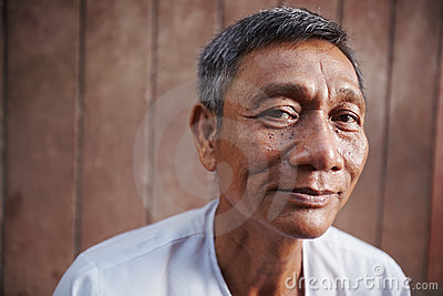 Asian old man looking at camera against brown wall