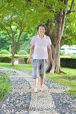 http://thumbs.dreamstime.com/x/asian-older-woman-walking-stone-walkway-park-42364447.jpg