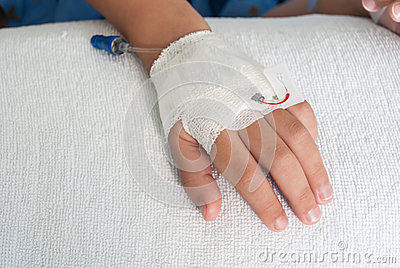 Asian patient boy hand with saline intravenous (iv) on hospital