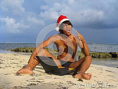 Asian Santa on beach with laptop