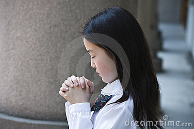 Asian schoolgirl praying