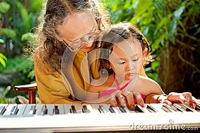 Asian senior woman teach child playing piano