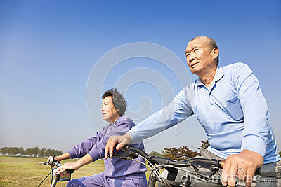 Asian seniors couple biking