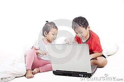 Asian sibling using laptop