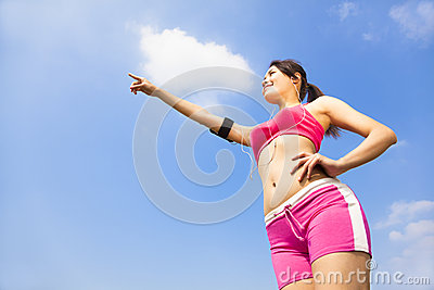 Asian smiling sporty woman watching and pointing far away