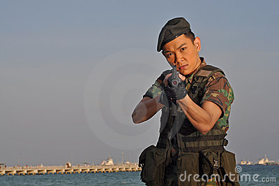 Asian Soldier pointing the rifle at viewer