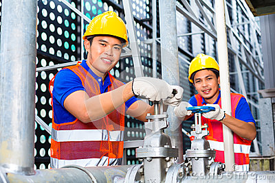 Asian Technicians or engineers working on valve