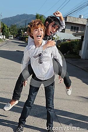 Asian teens piggyback on suburban street