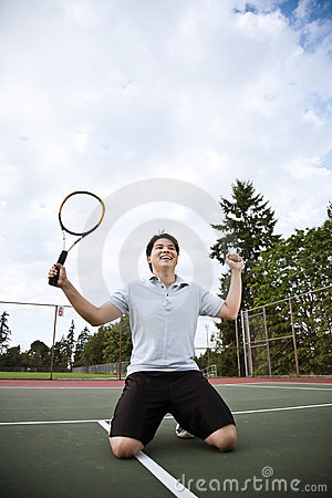Asian tennis player in joy after winning