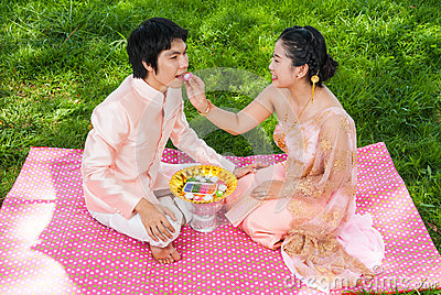 Asian Thai Bride Feeding her Cute Groom