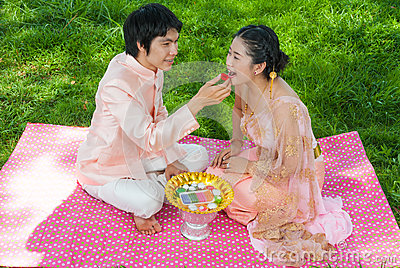 Asian Thai Groom Feeding his Cute Bride