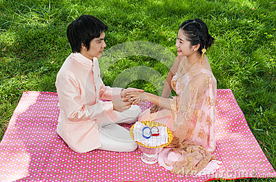 Asian Thai groom is wearing wedding ring to his bride in Thai ceremony