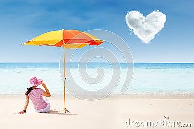 Asian tourist at beach under umbrella and love cloud