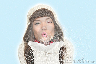 Asian winter woman blowing snow kiss