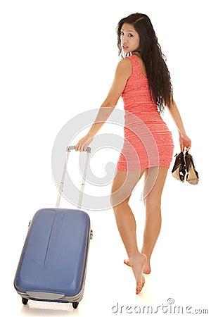 Asian woma walking away suitcase