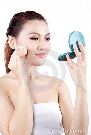 Asian woman applying powder on her face