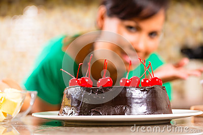 Asian woman baking  chocolate cake in kitchen