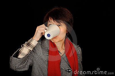 Asian woman drinking from cup