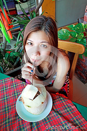 Asian woman drinking refreshment of young coconut