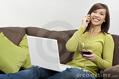 Asian Woman Drinking Wine on Phone Using Laptop