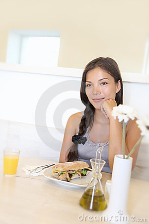Asian woman eating at cafe