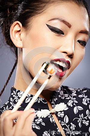 asian woman eating sushi,