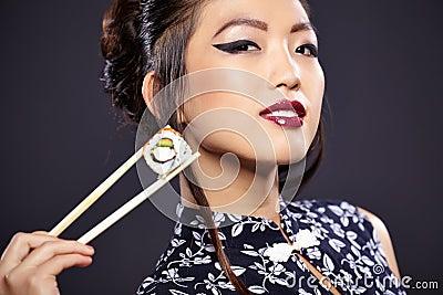 Asian woman eating sushi,