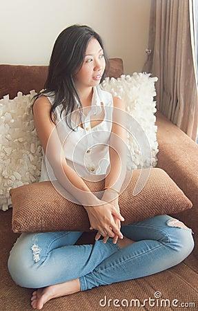 An Asian woman enjoy relaxing on a sofa